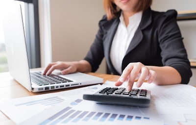 female accountant working with calculator in office